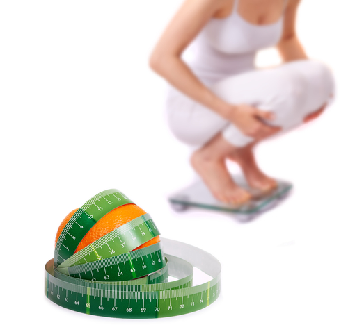 Weight loss. Girl on a bathroom scale - Isolated
